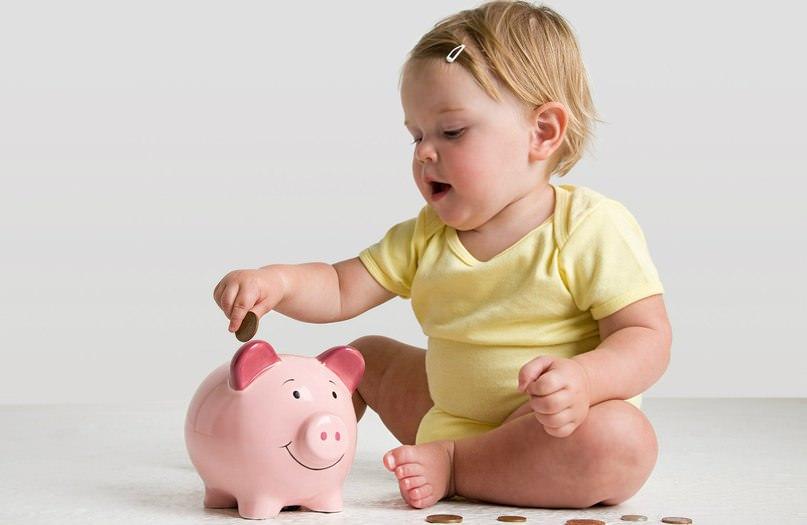 Ребенок бросает деньги в копилку